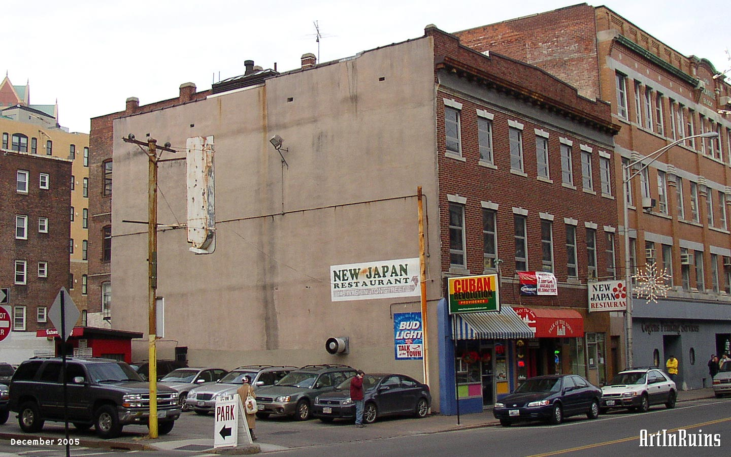 A three-story red-brick fronted commercial building seven windows wide. Windows have stone lintels and sills. The ground floor was occupied by three restaurant businesses with a mix of metal, wood, and brick facades.
