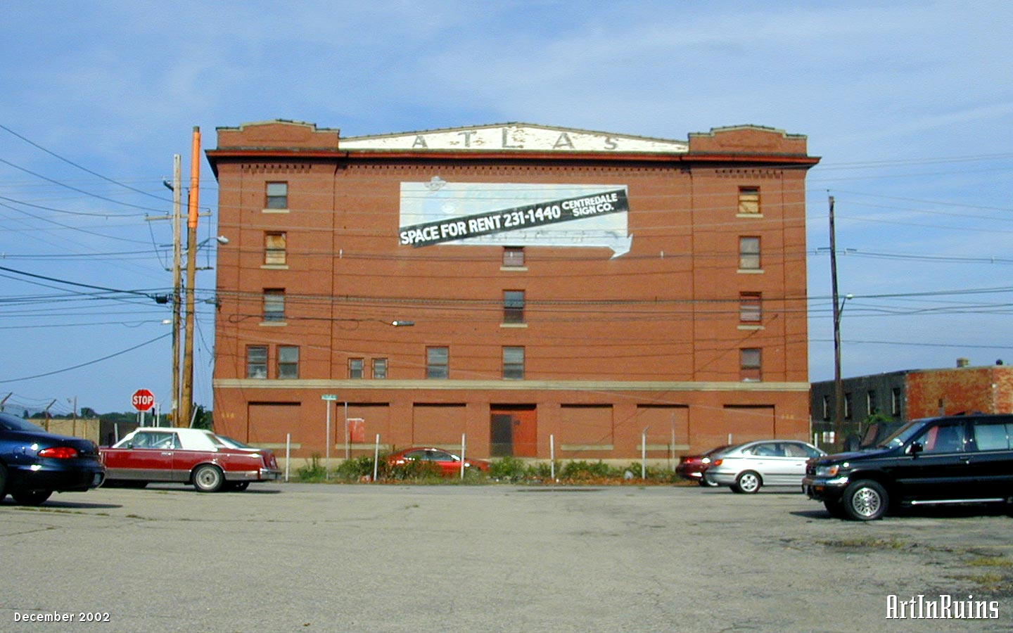 Two large, solidly built five-story warehouses along the Providence harbor waterfront. Red brick construction with small window openings, stone sills, and arched stone lintels on square plans with a few hundred feet between them. The warehouse facing the waterfront had giant white faded letters reading Terminal Warehouse Co.