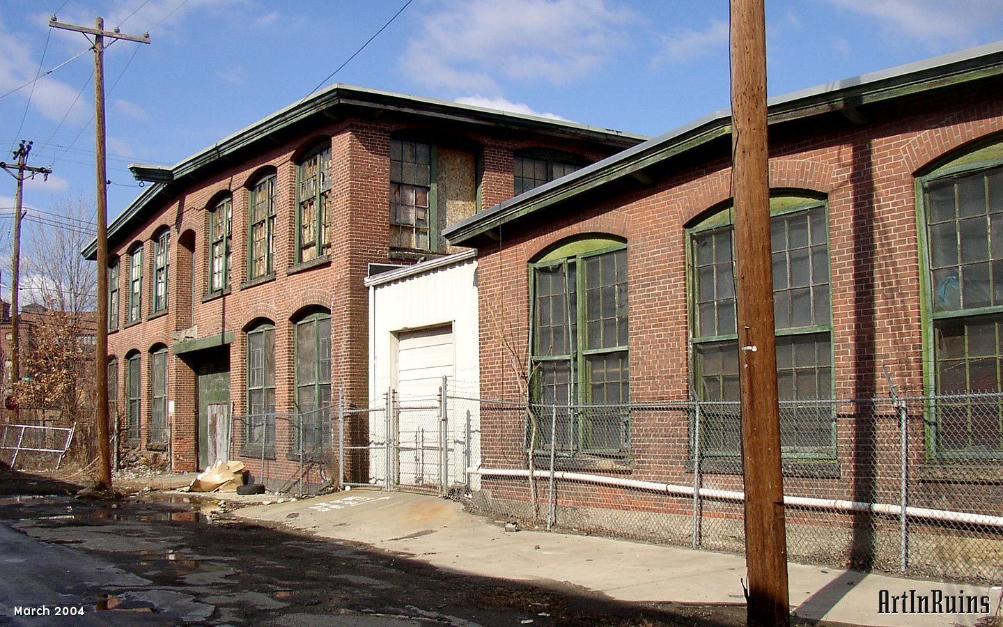 A two story L-shaped small complex of red brick mill buildings including a boiler house with large stack. Windows are double-hung, multi-pane style with arched lintels and granite sills. Brickwork has some slight decorative elements along the roof line to accent piers between windows.