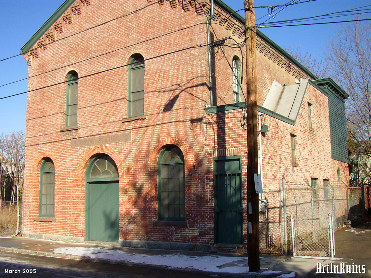 A small rectangular red brick former firehouse with central rounded arch double door entrance flanked by two smaller rounded arch windows. Two rounded arch windows are above with a simple gable roof and decorative brick corbelling along the roof edge