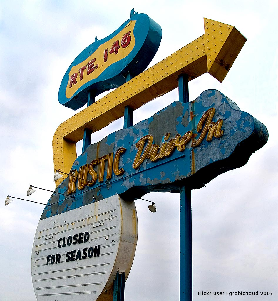 A side-of-the-highway Drive In movie theatre with a distinctive neon and multi-bulb sign featuring an arrow that runs from the bottom left up to the top and the sharp right and across the top
